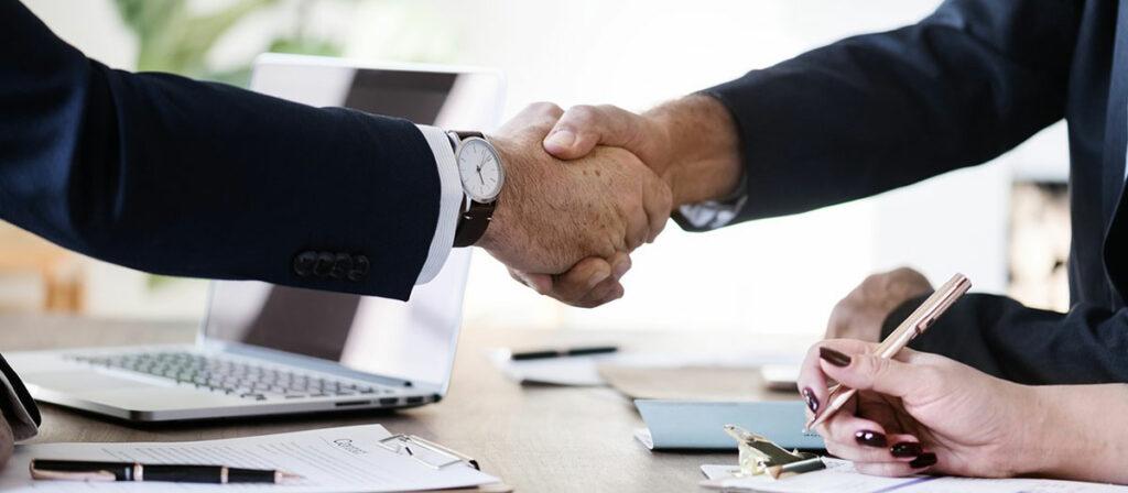 Duas pessoas apertando as mãos em uma reunião de prospecção de clientes.