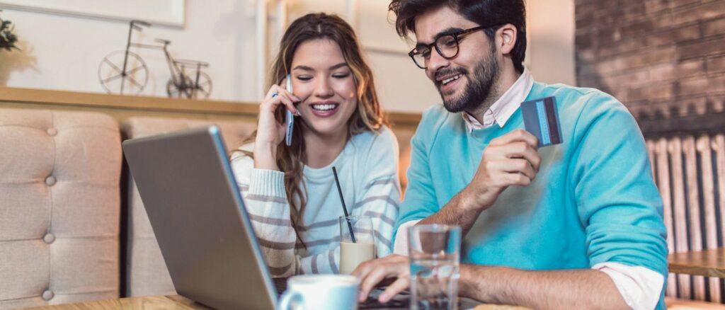 Um casal em frente ao notebook, analisando resultados de uma estratégia de atendimento online.