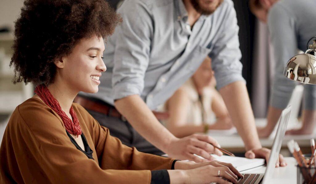 Duas pessoas conversando enquanto uma interage com o computador.