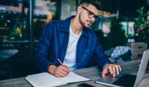 Homem sentado em uma mesa olhando a tela de um notebook. Analisando o dados do perfil do cliente.