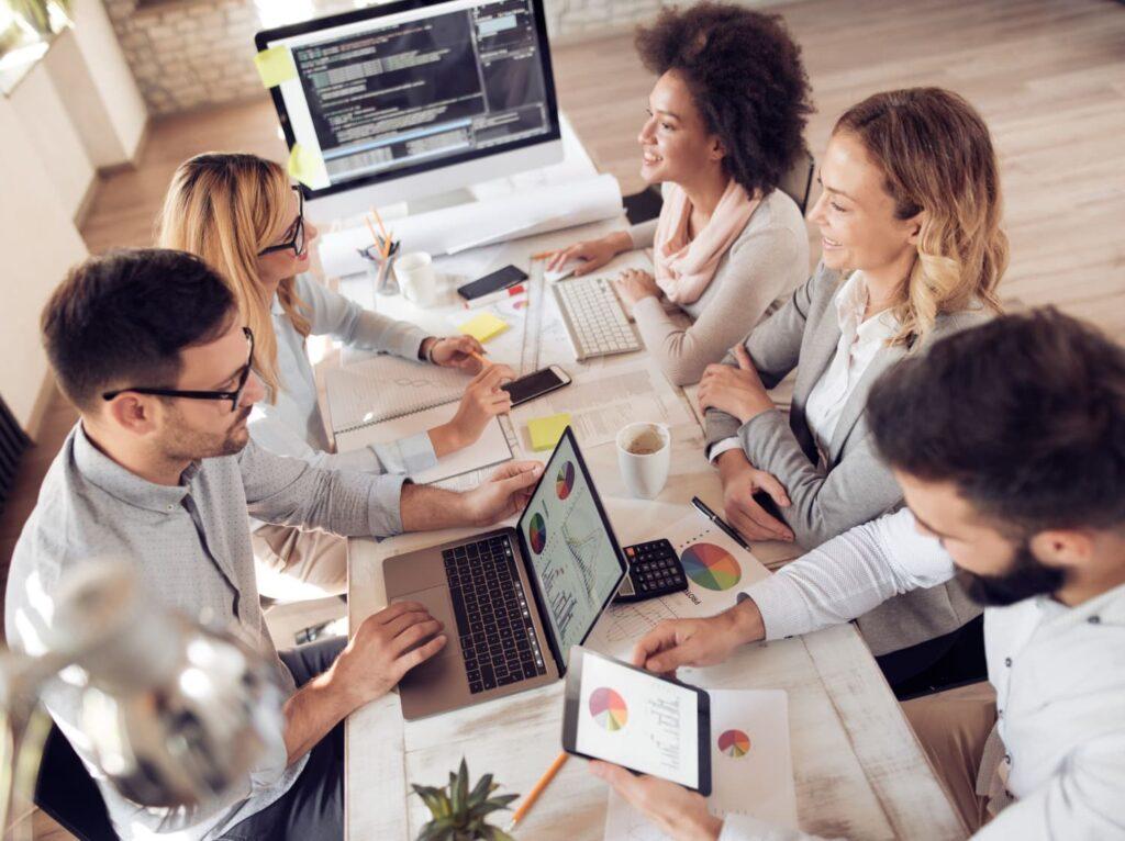 Um grupo de pessoas reunidas em uma mesa trabalhando.