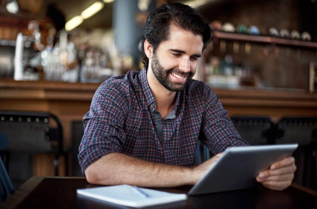 Homem sentado em uma mesa sorrindo enquanto olha seu tablet