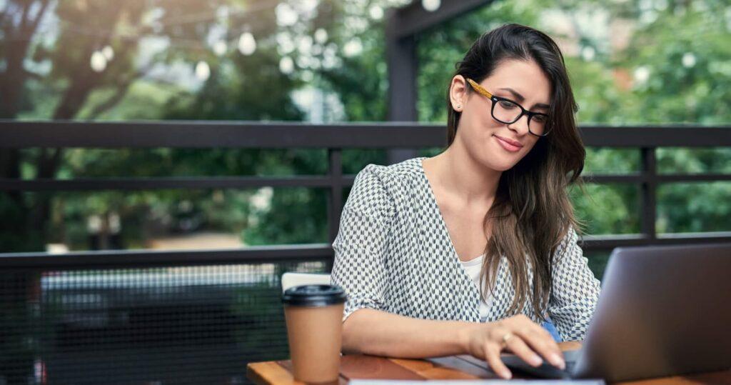 Mulher empresária com seu notebook tomando café em cima de uma mesa