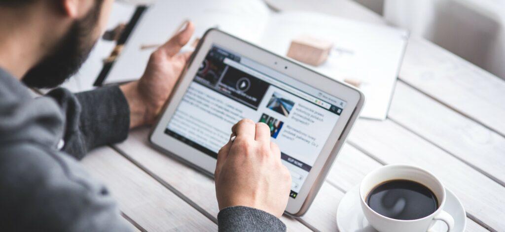 Pessoa segurando um tablet olhando a tela