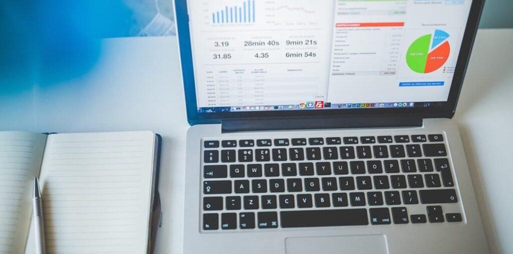 Macbook em cima de uma mesa mostrando alguns gráficos na tela.