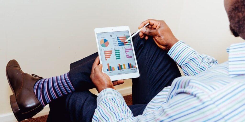Homem sentando olhando um tablet em sua tela alguns dados.