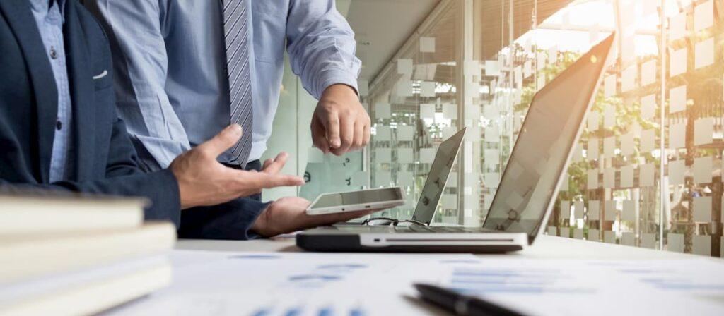 Dois empresários analisando alguns dados olhando a tela do notebook.